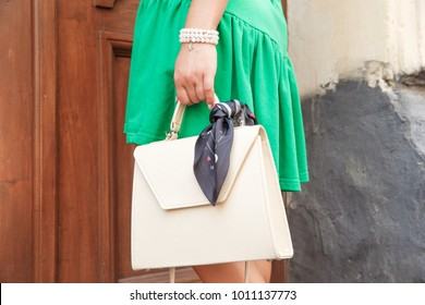 Stylish model in grass green cotton dress walking on the city streets with milky lether purse in hand. Woman in dress with leather handbag, street fashion look, summer outfit