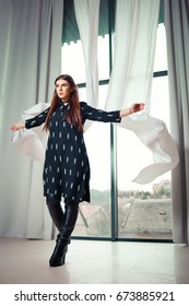 Stylish model with long black hair on the background of a large window