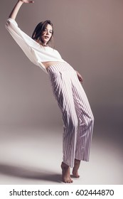 Stylish model in striped pants and white top in white studio