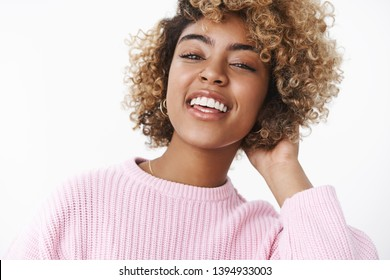 Stylish modern african-american girlfriend looking joyful and delighted at camera raising head proudly and smiling, laughing out loud touching curls on back, being satisfied over white background