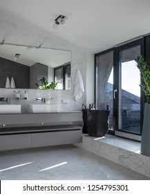 Stylish modern bathroom with light walls, large windows with glass door, tiled floor. There is a gray stand with two white sinks, wide mirror, hanging towels, lamps, green plant. It is sunny.