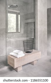 Stylish modern bathroom with tiled gray walls. There is a shower with a glass door, wooden stand with white towels ana a metal black basket. Vertical.