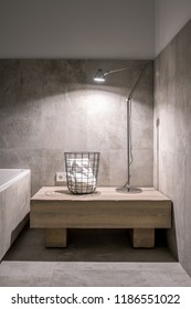 Stylish modern bathroom with white and tiled gray walls. There is a bath, light wooden stand with a metal black basket with a towel and a luminous lamp. Vertical.