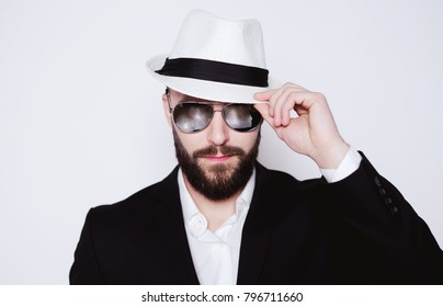 Stylish modern bearded man looking into the camera wearing sunglasses and a hat.