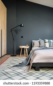 Stylish modern bedroom with dark and light walls and a parquet with a carpet on the floor. There is a bed with pillows and a coverlet and a plaid, black floor lamp, wooden wardrobe, small round table.