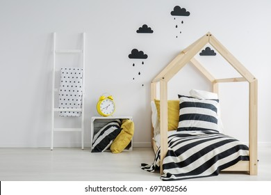 Stylish, modern child's bedroom with a large, yellow alarm clock, black rainy cloud stickers on the wall, and a wooden bed with striped bedding