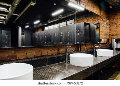 Stylish modern comfortable spacious locker room. Interior, nobody. Expensive quality materials, luxury. Loft design dressing room. Minimalist sink, faucet, metal shelf and mirror.