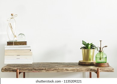 Stylish and modern decor with wooden console, books, plants and accessories. Copy space for inscription.
