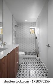 Stilvoll eingerichtetes Badezimmer mit Dusche und Hartholzfliesen.