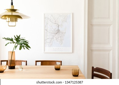 Stylish and modern dining room interior with mock up poster map, sharing table design chairs, gold pedant lamp and cups of coffee. White walls, wooden parquet. Tropical leafs in vase. Eclectic decor.