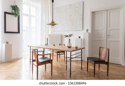 Stylish and modern dining room interior with design sharing table, chairs, gold pendant lamp, abstract paintings and elegant accessories. Tropical leafs in vase. Eclectic decor. Brown wooden parquet.