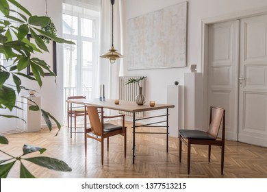 Stylish and modern dining room interior with design sharing table, chairs, gold pendant lamp, abstract paintings, plants and elegant accessories. Tropical leafs in vase. Eclectic home decor.