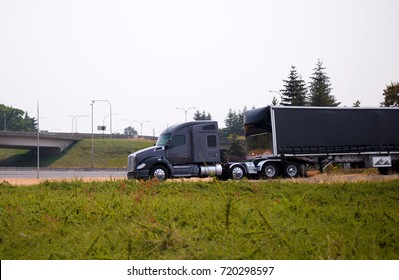 A stylish modern gray big rig semi truck with a large comfortable cabin and a powerful engine pulls a long black tilted semi trailer along the road to the entrance to the highway passing the overpass
