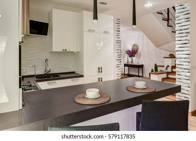 Stylish and modern interior of kitchen in beige, black and white colors. Two white cups on kitchen bar, two lamp over. Elements of stones, white wall and black chair around.