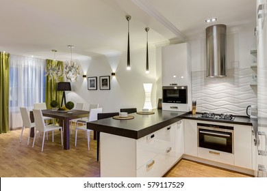 Stylish and modern interior of kitchen in white, black and green colors. Wooden table in corner of room and chair around. Two white cups on kitchen bar, lamp over.