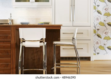 Stylish and modern kitchen with chairs set at an island in the middle. There is flowered wallpaper on the wall. Horizontal shot.