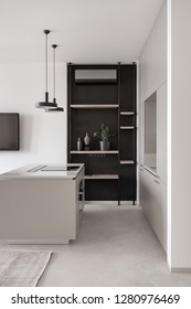 Stylish modern kitchen with light walls and a gray floor with a carpet. There is a kitchen island with a cooking surface, lockers, shelves, plant, hanging black lamps, dark TV, conditioner. Vertical.
