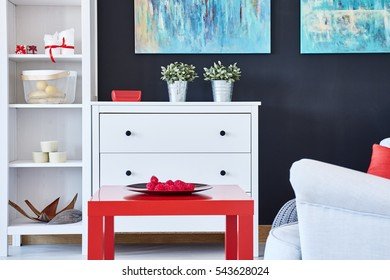Stylish modern living room with white furniture and red accessories