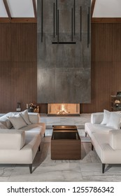 Stylish modern room with a burning fireplace, wooden wall, white ceiling with beams, tiled floor. There is a table with sofas with pillows, glass stand with vases, black bag with firewood, lamps.