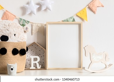 Stylish and modern scandinavian childroom interior with mock up photo or poster frame on the white shelf. Toys, teddy bear in basket, rocking horse  and hanging cotton colorful flags and stars. Blank.