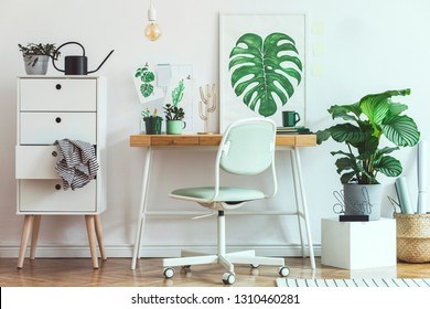 Stylish and modern scandinavian interior of home office desk with mock up poster frames, a lot of plants and office accessories. Modern composition of homeoffice desk.