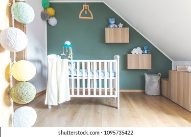 Stylish and modern scandinavian newborn baby room with toys, teddy bears, cotton ball lamps and baby cot. Modern green background wall.
