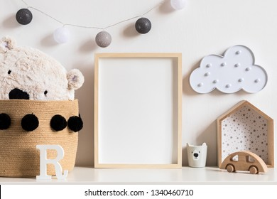 Stylish and modern scandinavian newborn baby interior with mock up photo or poster frame on the white shelf. Wooden toys, teddy bear, cup and hanging cotton lamps and star. Template. Blank. Real photo