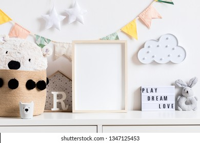Stylish and modern scandinavian newborn baby interior with mock up photo or poster frame on the white shelf. Toys, teddy bear, plush rabbit and hanging cotton flags, cloud and stars. Cozy decor.