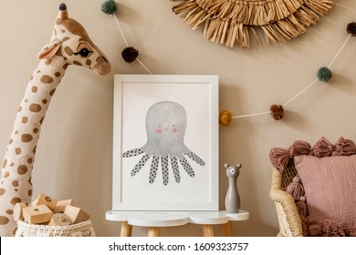 Stylish and modern scandinavian newborn baby interior with mock up photo frame on the small table. Toys, sofa, plush animal and hanging cotton colorful balls. Beige wall. Design home staging. Template