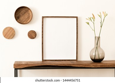 Stylish and modern scandinavian room interior with brown mock up poster frame, wooden console and rings on the wall, beautiful flowers in glassy vase. Design composition of home interior. Home decor. - Shutterstock ID 1444456751