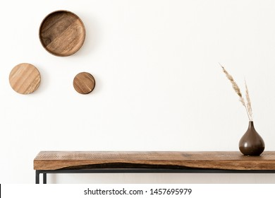 Stylish and modern scandinavian room interior with wooden console and rings on the wall, flowers in brown vase. Design composition of home interior. White walls, copy space. Home decor. Template.