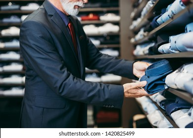 Stylish and modern senior business man choosing and buying shirt in expensive store.