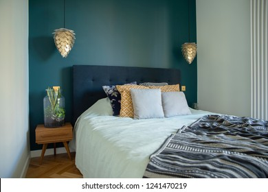 Stylish and modern sunny bedroom with small wooden table , white bedding and colours pilows. Space with blue walls and brown wooden parquet.