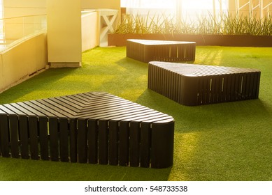 Stylish modern triangle shaped brown wooden bench indoor furniture on artificial grass beside the window