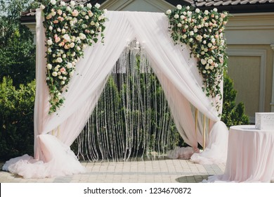 Stylish modern wedding arch with roses,tulle,stones, floral decorations at wedding reception outdoors. Luxury adorning.