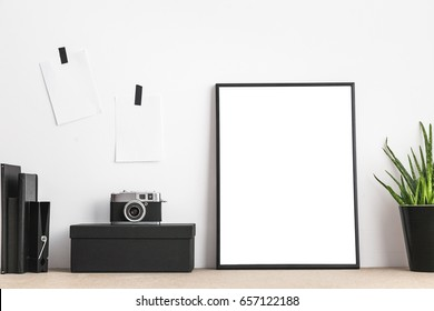 Stylish and modern workspace with black empty frame, sticky notes, books and camera on home or studio.