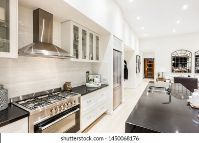 Una cocina modular de diseño con frigorífico al lado y un mostrador de cocina frente a las estanterías y la estufa.
