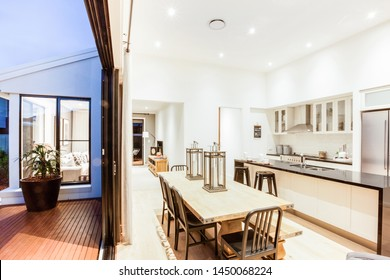 Stylish modular kitchen with a snack counter and a dining table with a contemporary style table top.