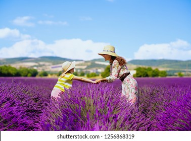stylish mother and daughter at lavender field in Provence, France stand holding hands. Family spending fun day in endless plains of lavender. Perfect summer day ideal to travel with family