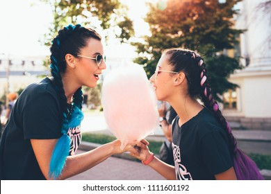 stylish mother and teenage daughter eating candy floss , focus on the foreground