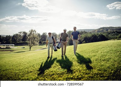 Stylish multicultural friends spending time together while playing golf on golf course
