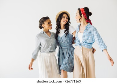 stylish multicultural women in retro clothing looking at each other isolated on grey