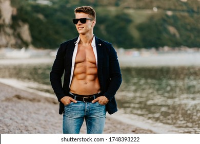 Stylish muscular handsome man wearing jacket and sunglasses outdoors. Sexy man with naked body and jacket walk on beach.