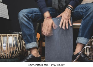 A stylish musician in denim and double monk shoes plays the Cajon, a Peruvian drum used commonly with Spain's Flamenco dance.