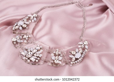 Stylish necklace with stones on pink fabric background.