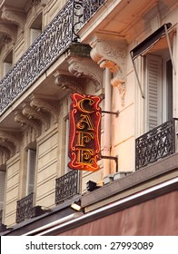 Stylish  neon Cafe sign in shopping district of Paris with open window and Balcony