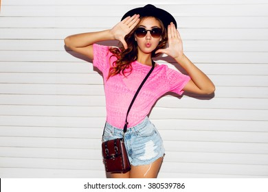 Stylish night flash fashion portrait of trendy  casual young  woman in pink neon  t-shirt , black hat, stylish shirts posing near white urban  wall along .