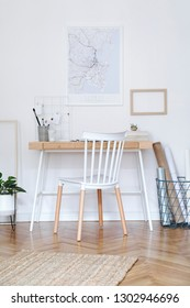 Stylish nordic home interior with creative wooden desk, grey bookstand with accessories, design and modern furniture. Open space and living room for artist, designer. Mockup poster frame.