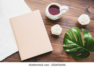 A stylish notebook, a cup of tea and a philodendron leaf on the table. The atmosphere of creativity. Place for text