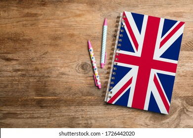 Stylish notebook and pens on wooden table, flat lay with space for text. Learning English